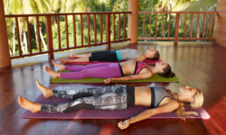 Shot of yoga class with women lying on floor. Yoga class relaxing in the Corpse pose, Savasana.