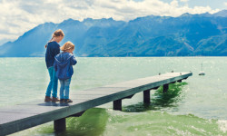 Cute kids playing by the lake, resting on a pier, wearing blue clothes, toned image